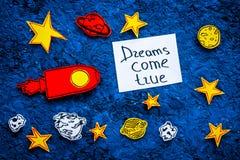 Motywacyjny plakat Sen przychodzą prawdziwego ręki literowanie przy błękitnym kosmosu tłem z rakiety i gwiazd odgórnym widokiem fotografia stock