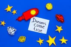 Motywacyjny plakat Sen przychodzą prawdziwego ręki literowanie przy błękitnym kosmosu tłem z rakiety i gwiazd odgórnym widokiem zdjęcia royalty free