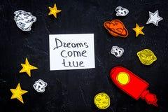 Motywacyjny plakat Sen przychodzą prawdziwego ręki literowanie przy czarnym kosmosu tłem z rakiety i gwiazd odgórnym widokiem fotografia stock