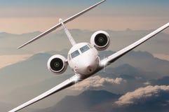 Mouche d'avion au-dessus des nuages et de la montagne d'Alpes sur le coucher du soleil Vue de face d'un grand avion de passager o Image stock