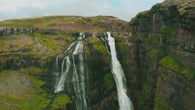 Mouche de l'Islande par l'antenne d'une cascade de Glymur avec une fille s'asseyant près de la falaise clips vidéos