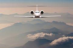 Mouche de luxe d'avion au-dessus des nuages et de la montagne d'Alpes sur le coucher du soleil Vue de face d'un grand avion de pa Photos libres de droits
