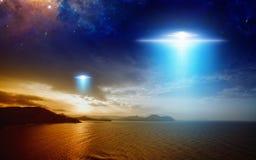 Mouche extraterrestre de vaisseau spatial d'étrangers au-dessus de mer de coucher du soleil Photographie stock libre de droits