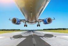 Mouche inférieure haute étroite d'avion de passager au-dessus de la piste par temps beau Photographie stock