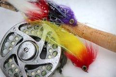 Mouches, tige et bobine de pêche de mouche de Pike dans la neige images libres de droits