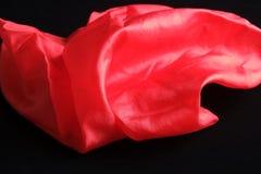 Mouchoir en soie rouge vif brillant sur le velours noir Photo libre de droits