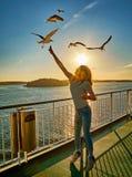 Mouettes de alimentation de jeune fille dans la fusée du coucher de soleil à bord d'un ferry en Scandinavie Photo stock