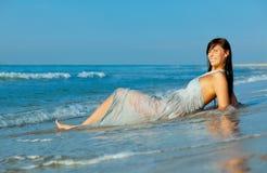 Mouillez la femme de bord de la mer de robe Photographie stock