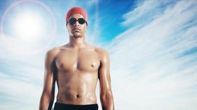 Mouillez le nageur attirant d'Afro-américain contre le ciel avec l'éclat de lentille image stock