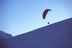 滑翔伞在mouintans的冬天,与滑翔伞的日落 免版税库存照片
