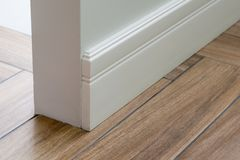 Moulding in the corner. Light matte wall with tiles immitating hardwood flooring.  royalty free stock photo