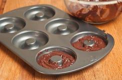Moule de cuisson en métal étant rempli de pâte crue de chocolat photo stock