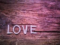 Moule de mots d'amour par l'argile sur le fond en bois approximatif Photos stock