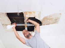 Moule de nettoyage d'homme sur le plafond Les panneaux de plafond ont endommagé le trou énorme dedans photo libre de droits
