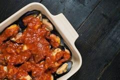 Moules crues avec la sauce tomate sur le fond noir, faisant cuire photos libres de droits