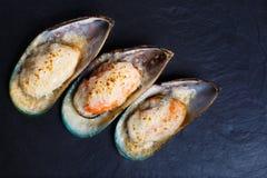 Moules cuites au four de mollusques et crustacés sur le fond en pierre foncé Seaf délicieux Photos stock