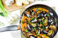Moules délicieuses de fruits de mer avec de la sauce rouge et les oignons verts dans une casserole Photographie stock