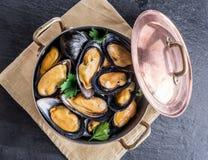 Moules dans la casserole de cuivre sur le fond de graphite Images stock