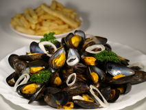 Moules frites. Fried mussels on a plate on white background Royalty Free Stock Photography