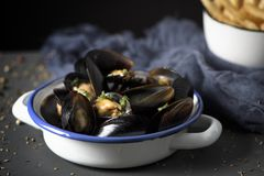 Moules-frites, typical Belgian mussels and fries. Moules-frites, mussels and fries typical of Belgium, on a rustic wooden table royalty free stock image