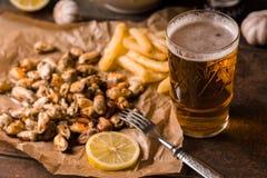 Moules, pommes de terre frites sur le parchemin et bière dans un verre Images stock