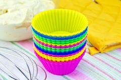 Moules pour des petits gâteaux avec le mélangeur de potholder sur le tissu Photographie stock libre de droits
