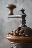 Moulin à café avec des grains de café à l'arrière-plan brouillé Photo stock