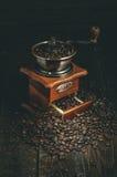 Moulin à café avec des grains de café sur la table foncée Rétro fond photographie stock