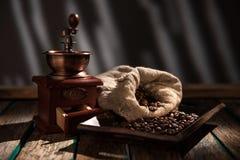 Moulin à café sur le fond rustique foncé Table en bois Photographie stock