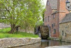 Moulin à eau de village avec les bâtiments en pierre à côté de la rivière Photos stock