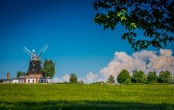 Moulin à vent au printemps derrière un champ de grain photo stock