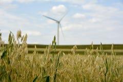 Moulin à vent blanc, ciel bleu, nuages blancs, montagnes vertes et eaux photos libres de droits