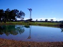 Moulin à vent, cloche et étang Photographie stock