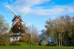 Moulin à vent en bois traditionnel dans un jardin luxuriant Images libres de droits