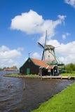 Moulin à vent néerlandais au-dessus des eaux de rivière Photographie stock