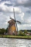 Moulin à vent néerlandais aux canaux avant orage d'été Images libres de droits