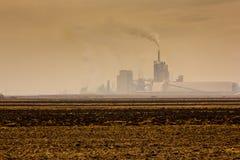 Moulin d'engrais polluant l'atmosphère avec de la fumée et le brouillard enfumé Photographie stock