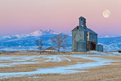 Moulin de grain d'abandon au lever de soleil le long de la chaîne de montagne Image stock
