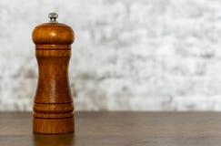 Moulin de poivre en bois sur la table en bois sur le fond gris de mur photo stock