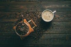 Moulin et tasse à café avec des haricots sur le fond foncé Vue supérieure photos stock