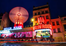 Moulin Rouge cabaret, Paris, France at night. Moulin Rouge cabaret illuminated at nighttime in Paris, France stock photo