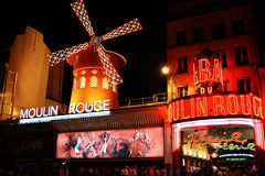 The Moulin Rouge famous cabaret. PARIS - AUGUST 23: People in long queue for tickets, in front of The Moulin Rouge, famous cabaret and theater on August 23, 2010 stock photography