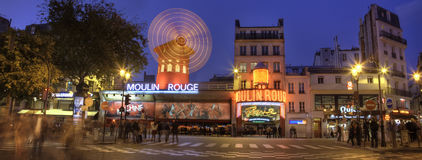 Moulin Rouge, Paris by Night panorama. A panorama of the famous Moulin Rouge cabaret and illuminated mill on Boulevard de Clichy. Shot in the blue hour with long Royalty Free Stock Photo