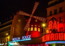 Moulin Rouge is the world famous cabaret in Paris at Montmartre. A very effective night light and rotating blades of the windmill. Moulin Rouge is the world stock photo
