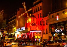 Moulin Rouge is the world famous cabaret in Paris at Montmartre. A very effective night light and rotating blades of the windmill. Moulin Rouge is the world royalty free stock images