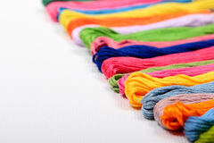 Mouline on canvas. Colorful cotton craft threads on white canvas with copy space Stock Photography