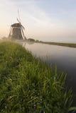 Moulins à vent brumeux sur une digue Photographie stock libre de droits