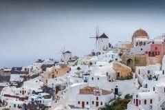 Moulins à vent dans le village coloré et de pictoresque d'Oia un jour pluvieux rare image libre de droits