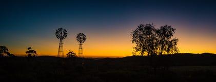 Moulins à vent de ferme silhouettés contre le Soleil Levant Photographie stock