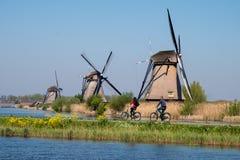 Moulins à vent historiques avec des cyclistes faisant un cycle dans le premier plan, chez Kinderdijk, la Hollande, Pays-Bas, un s image libre de droits